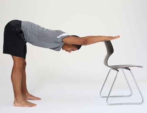 Mann hat Hände an Stuhllehne und dehnt den Rücken