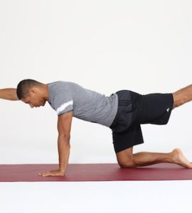 Mann macht Rückenübung auf allen Vieren All Fours auf dunkelroter Trainingsmatte