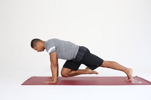 Mann macht Mountain Climbers auf dunkelroter Trainingsmatte - Plank Varianten