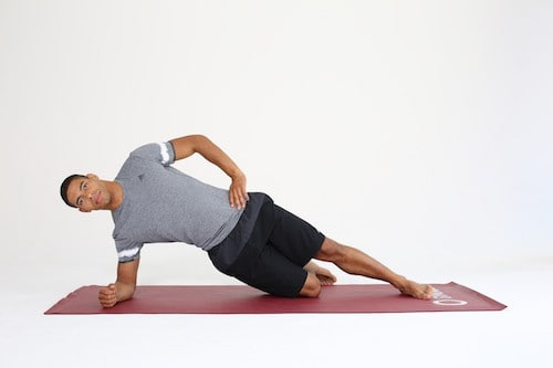 Mann macht Side Plank auf dunkelroter Trainingsmatte