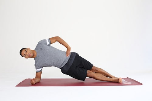 Mann macht seitlichen Unterarmstütz die Übunge Side Plank auf roter Trainingsmatte -Plank Varianten