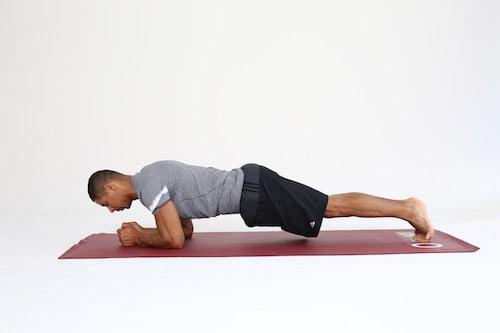 Mann macht Plank Shift auf dunkelroter Trainingsmatte
