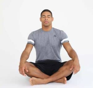 Mann sitzt im Schneidersitz mit geschlossenen Augen und entspannt sich