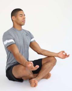 Mann sitzt auf Trainingsmatte in Schneidersitz in Entspannungsposition und macht progressive Muskelrelaxation