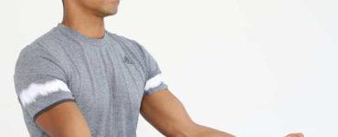 Mann sitzt im Schneidersitz und macht progressive Muskelrelaxation