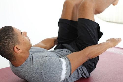Mann macht Crunches auf dunkelroter Trainingsmatte