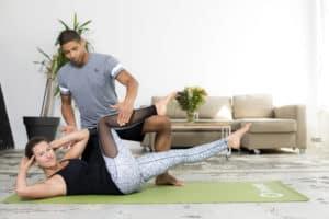 Patricio Escher mit einer Jungen Frau leitet eine Bauchübung an im Präventionsprogramm