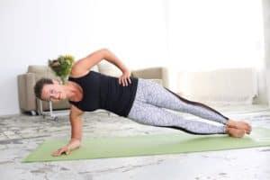 Frau macht Side Plank auf hellgrüner Trainingsmatte
