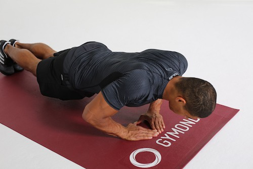 Mann macht Diamond Push Ups auf dunkelroter Trainingsmatte