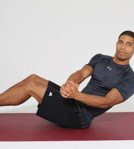 Mann macht Russian Twists auf dunkelroter Trainingsmatte
