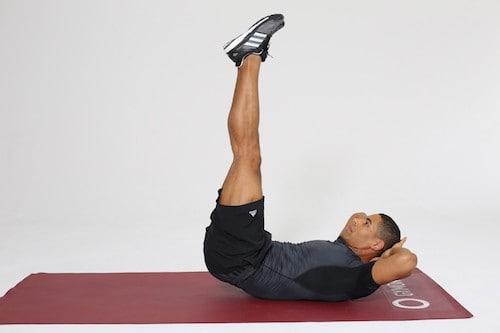 Mann macht Reverse Crunches auf dunkelroter Trainingsmatte