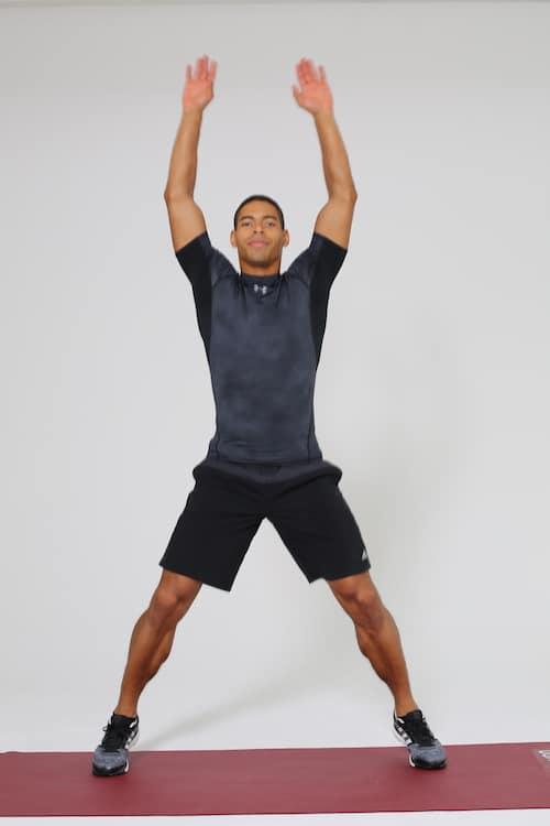 Mann springt Jumping Jacks auf dunkelroter trainingsmatte