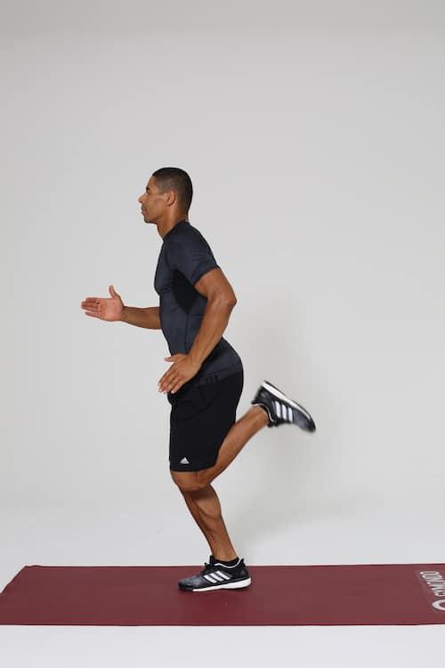 Mann joggt auf dunkelroter trainingsmatte