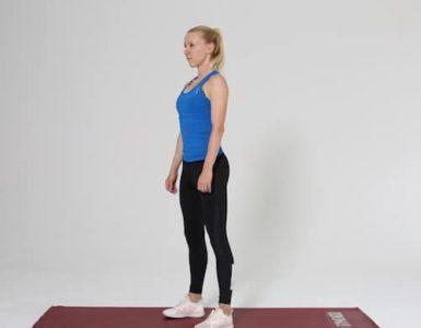 Frau macht Squat Ausgangsposition auf roter Trainingsmatte