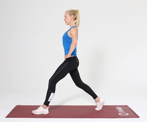 Frau in der Ausgangsposition für Lunges auf roter Trainingsmatte
