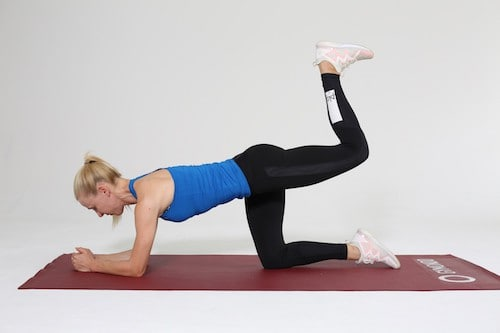 Frau macht Knee raise auf roter Trainingsmatte