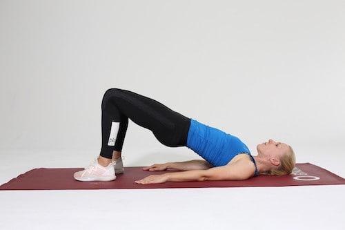 Frau macht Hip Lift auf roter Trainingsmatte