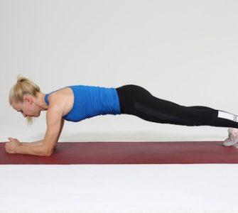 Frau macht Plank auf roter Trainingsmatte
