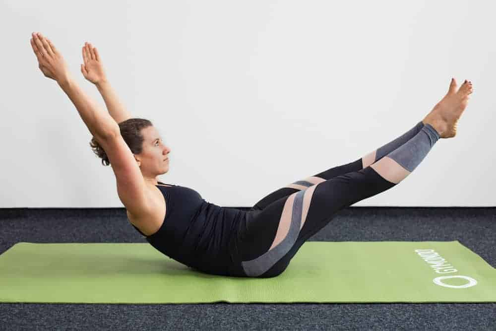 Junge Frau in Rückenlage mit angehobenen Beinen auf einer hellgrünen Trainingsmatte macht Pilates Double Leg Stretch