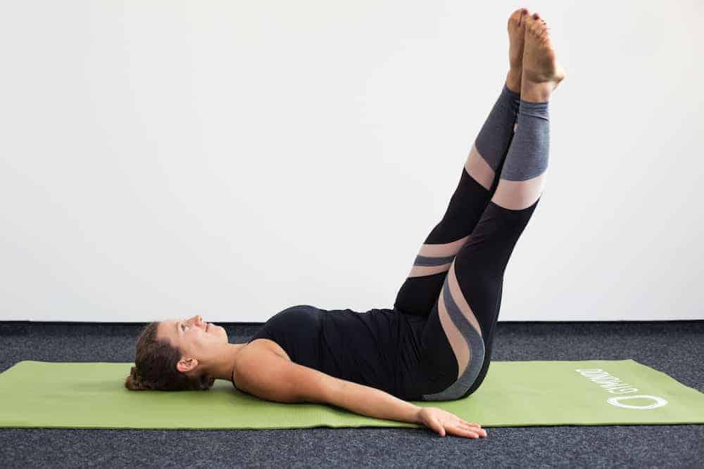 Junge Frau in Rückenlage auf einer hellgrünen Trainingsmatte macht Pilates Corkscrew