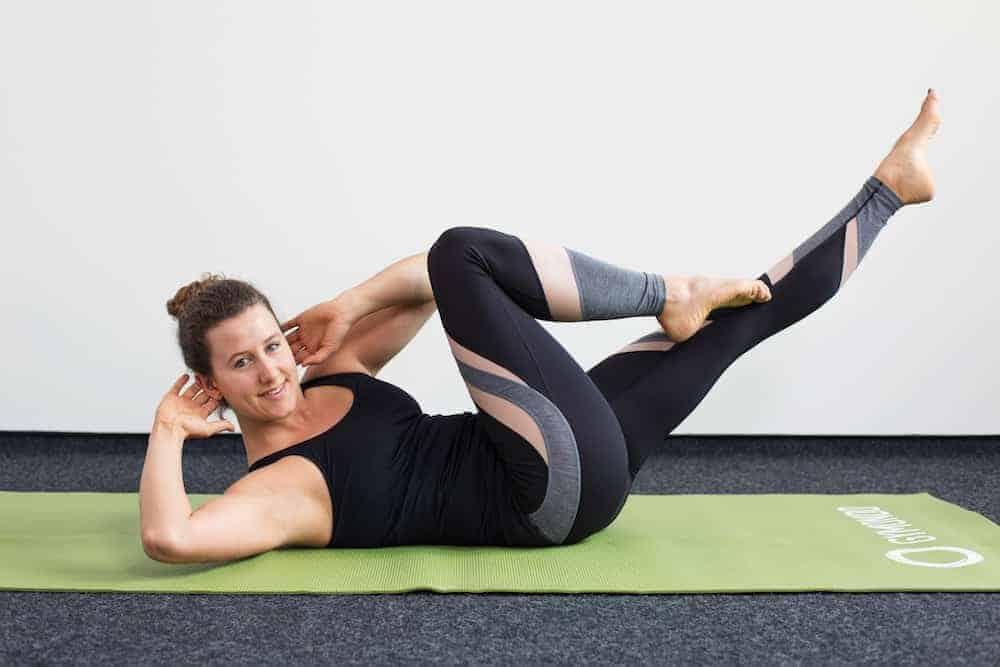 Junge Frau in Rückenlage auf einer hellgrünen Trainingsmatte macht Pilates Criss Cross