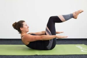 Junge Frau in Rückenlage mit angehobenen Beinen auf einer hellgrünen Trainingsmatte macht Pilates Hundred