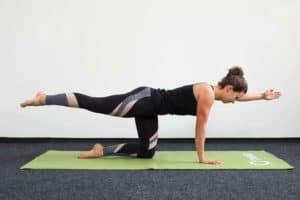 Junge Frau auf allen Vieren auf einer hellgrünen Trainingsmatte macht Pilates Quadruped