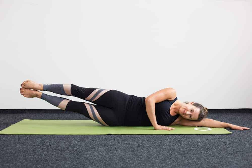 Junge Frau in Rückenlage auf einer hellgrünen Trainingsmatte macht Pilates Single Leg Lift und Double Leg Lift