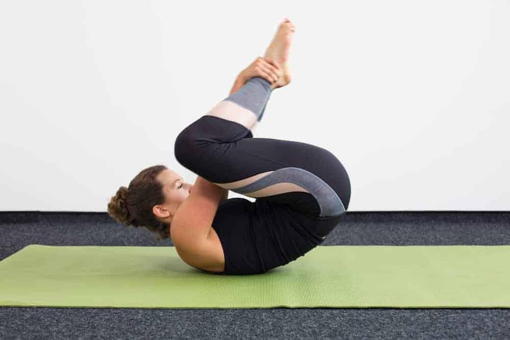 Junge Frau in Rückenlage auf einer hellgrünen Trainingsmatte macht Pilates Rolling Like a Ball