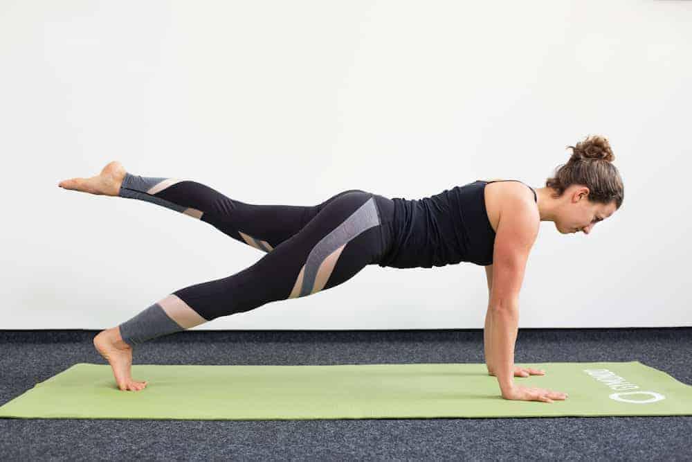 Junge Frau in Liegestützposition auf einer hellgrünen Trainingsmatte macht Pilates Leg Pull Front