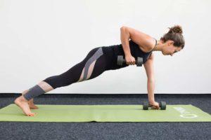 Junge Frau in Liegestützposition auf einer hellgrünen Trainingsmatte zieht mit Kurzhanteln einen Arm hoch
