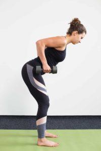 Junge Frau auf einer hellgrünen Trainingsmatte macht Row mit Kurzhanteln