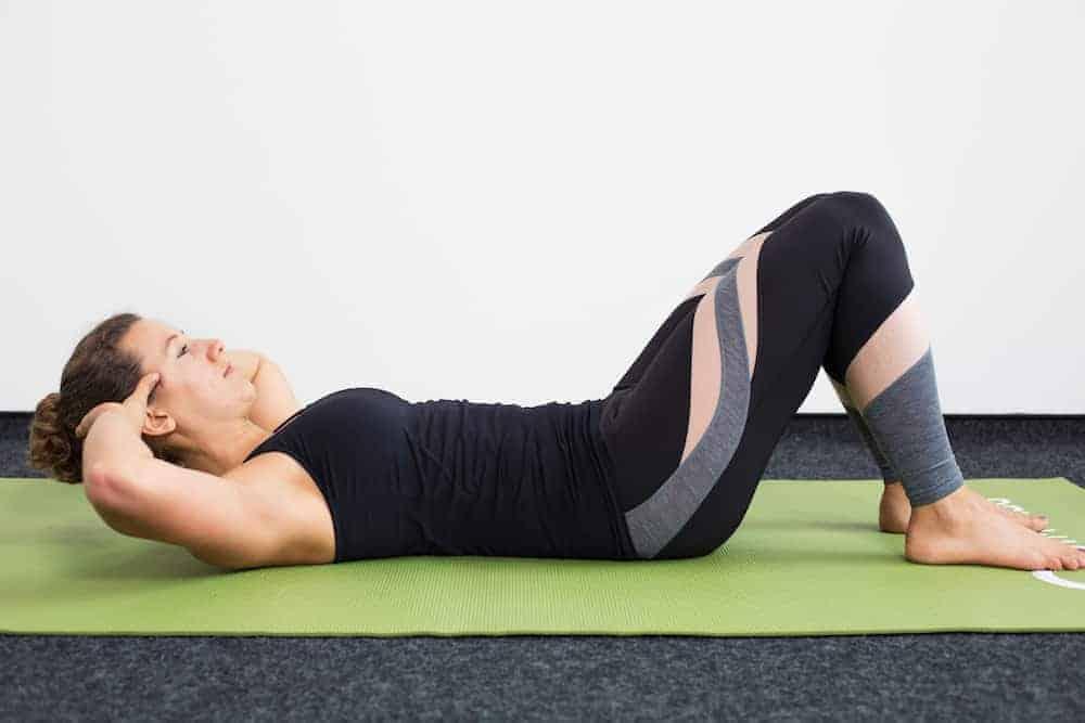 Junge Frau in Rückenlage auf einer hellgrünen Trainingsmatte macht Crunches Ausgangsposition