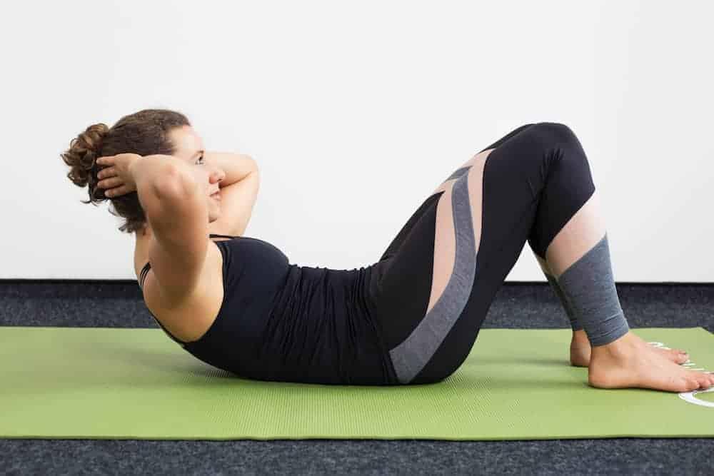Junge Frau in Rückenlage auf einer hellgrünen Trainingsmatte macht Crunches