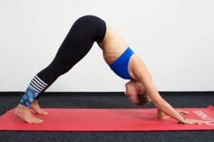 Junge Frau auf einer roten Trainingsmatte macht den Herabschauenden Hund aus dem Yoga