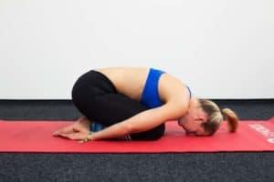 Junge Frau auf einer roten Trainingsmatte macht das Kind, die Haltung des Kindes aus dem Yoga