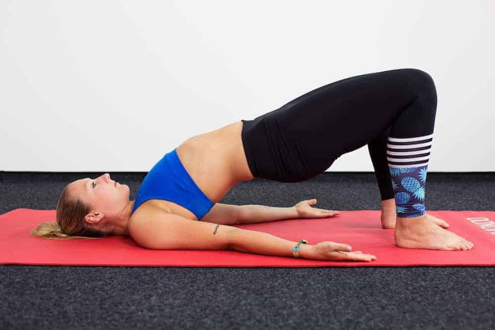 Junge Frau auf einer roten Trainingsmatte macht die Brücke aus dem Yoga