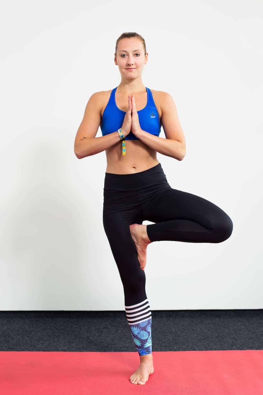 Junge Frau auf einer roten Trainingsmatte macht den Baum aus dem Yoga