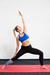 Junge Frau auf einer roten Trainingsmatte macht den Sonnenkrieger aus dem Yoga