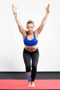 Junge Frau auf einer roten Trainingsmatte macht den Stuhl aus dem Yoga