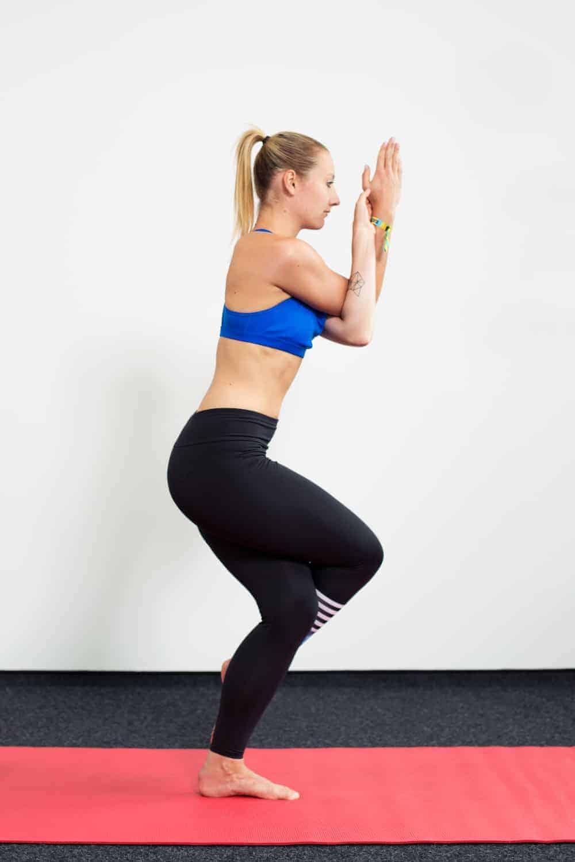 Frau in Sportkleidung auf roter Trainingsmatte macht Detox Yoga der Adler