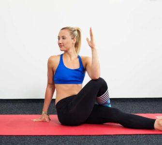 Junge Frau auf roter Trainingsmatte macht Yoga den sitzenden Twist