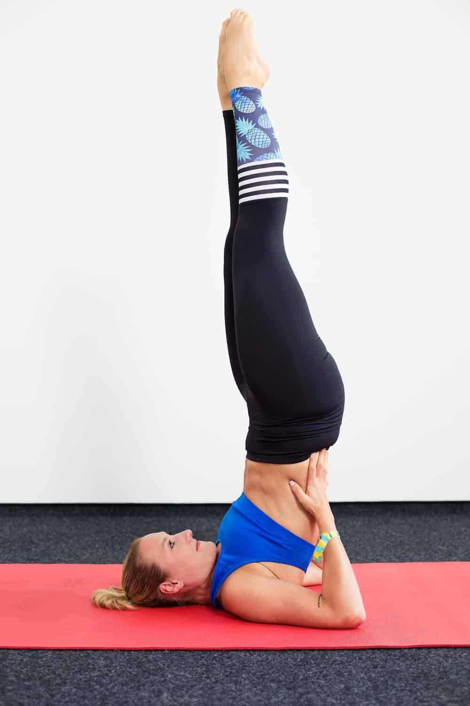 Frau in Sportkleidung auf roter Trainingsmatte macht Detox Yoga den Schulterstand