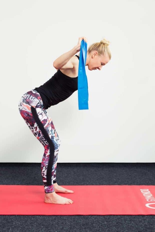 Frau in Sportkleidung steht vorgebeugt auf roter Trainingsmatte mit blauem Theraband und macht Lat Zug
