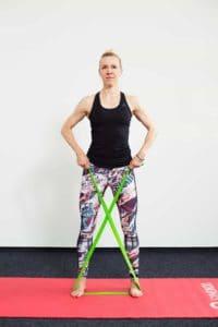 Frau mit Theraband auf Trainingsmatte steht frontal in Ausgangsposition für die Übung Armheben diagonal mit dem Theraband