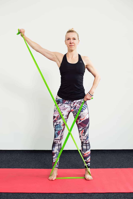 Frau auf roter Trainingsmatte steht frontal und macht Armheben diagonal mit dem Theraband
