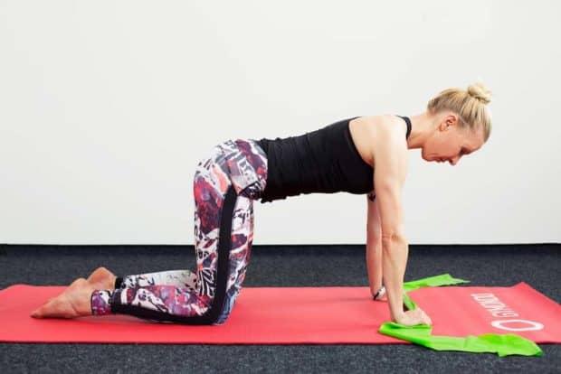 Frau auf roter Trainingsmatte seitlich auf allen Vieren macht Oberkörper Twist mit dem Theraband
