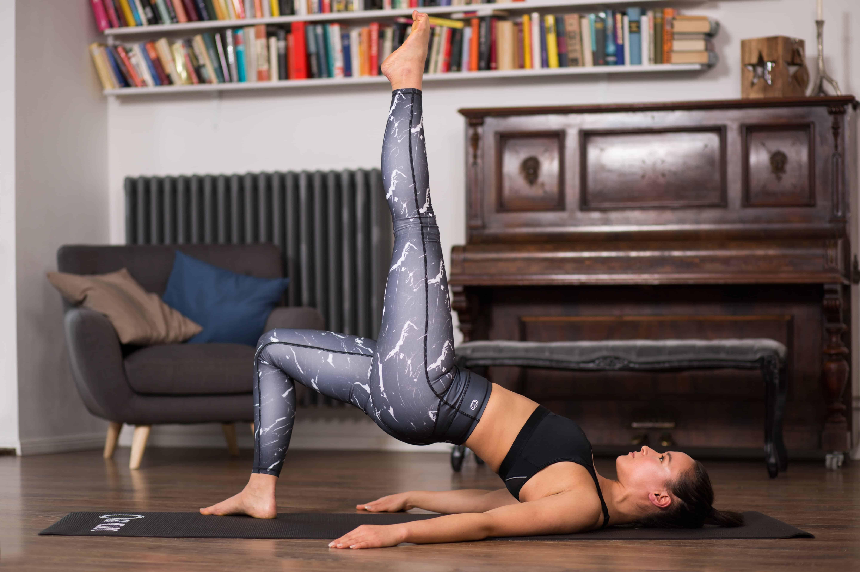 Frau macht Pilates Bridging, ein Bein ist nach oben gestreckt