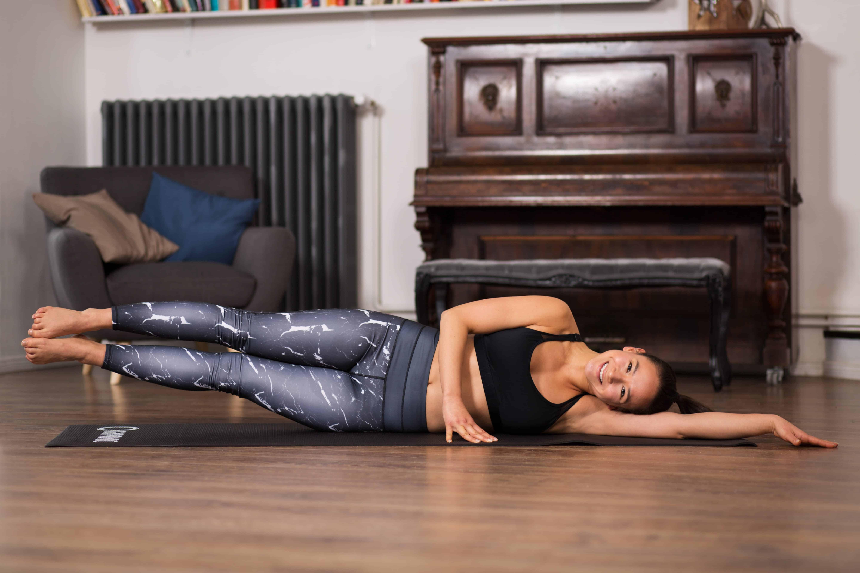 Frau macht Pilates Übung Side Kick