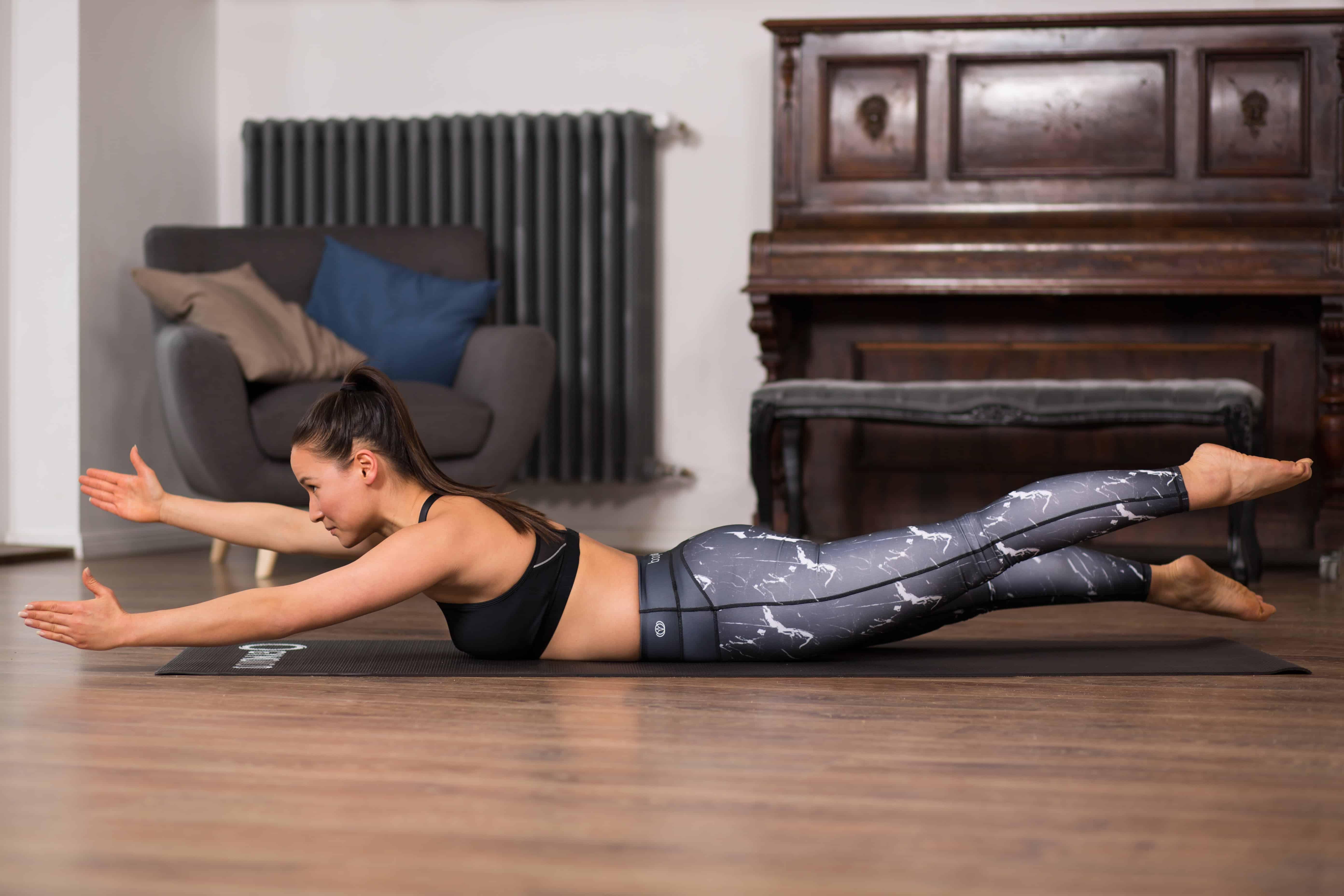 Frau macht Übung Swimming aus dem Pilates